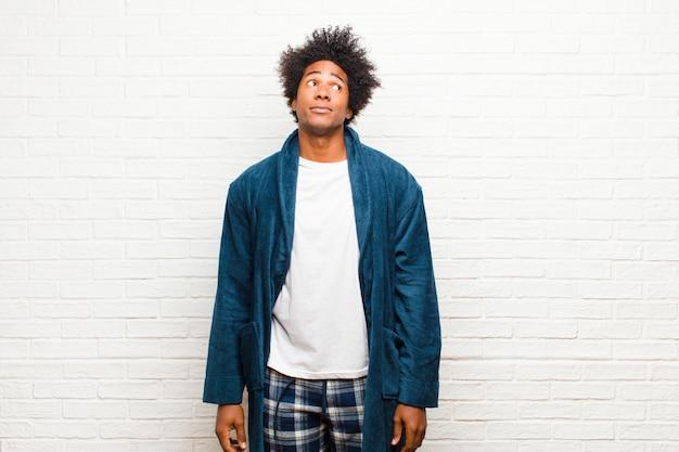 Jeune homme noir portant un pyjama avec une robe à la recherche perplexe et confuse, se demandant ou essayant de résoudre un problème ou pensant au mur de briques