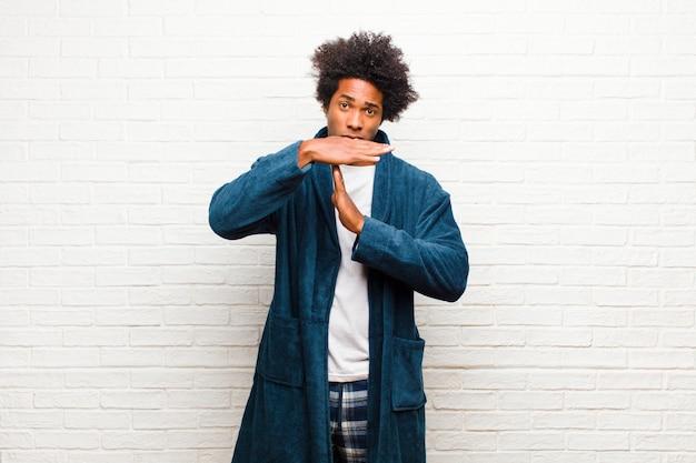 Jeune homme noir portant un pyjama avec une robe à la recherche de sérieux, de poupe, de colère et de mécontentement, faisant signe de temps mort