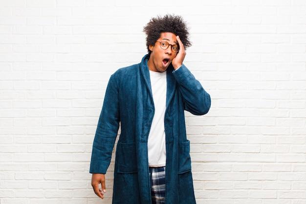 Jeune homme noir portant un pyjama avec une robe se sentant choqué et étonné, se tenant face à face avec incrédulité, la bouche grande ouverte contre le mur de briques