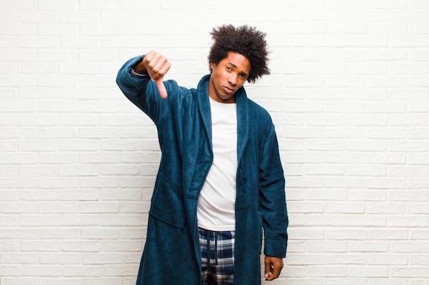 Jeune homme noir portant un pyjama avec une robe se sentant en croix, en colère, ennuyé, déçu ou contrarié, montrant les pouces vers le bas avec un regard sérieux contre le mur de briques