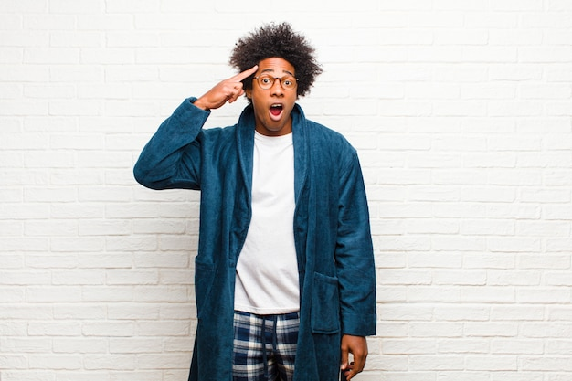 Jeune homme noir portant un pyjama avec une robe semblant surpris, bouche bée, choqué, réalisant une nouvelle pensée, idée ou contre un mur de briques