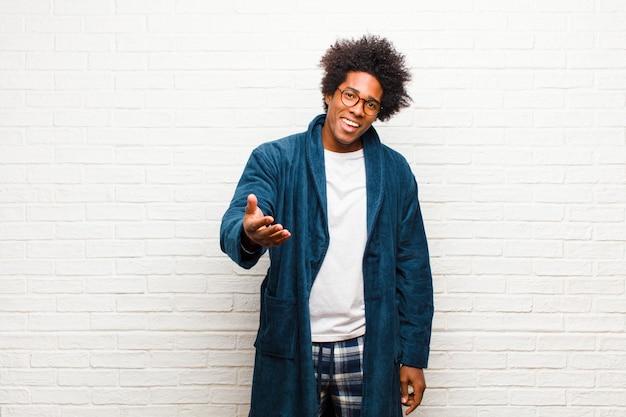 Jeune homme noir portant un pyjama avec une robe souriante, l'air heureux, confiant et amical, offrant une poignée de main pour conclure un accord, coopérant sur un mur de briques