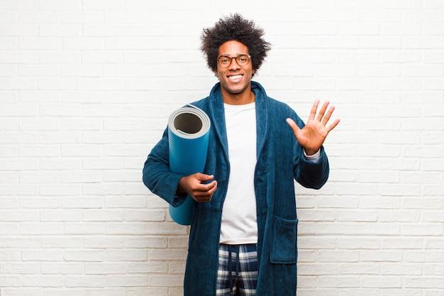Jeune homme noir portant un pyjama avec un tapis de yoga