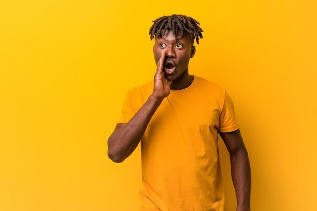 Jeune homme noir portant des rastas sur fond jaune dit une nouvelle secrète sur le freinage à chaud et regarde de côté