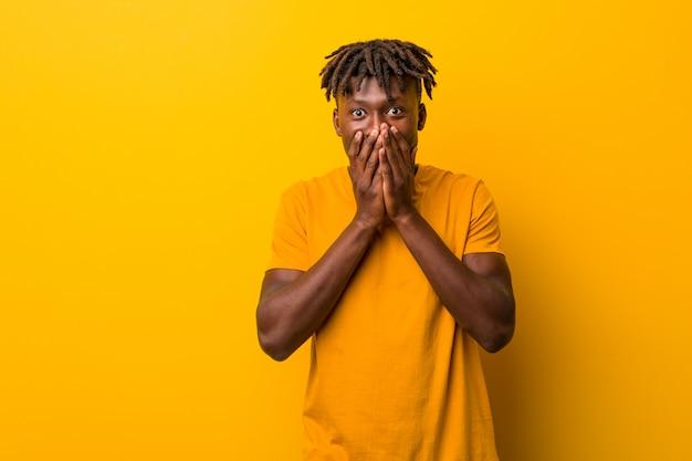 Jeune homme noir portant des rastas sur fond jaune en riant de quelque chose, se couvrant la bouche avec les mains.