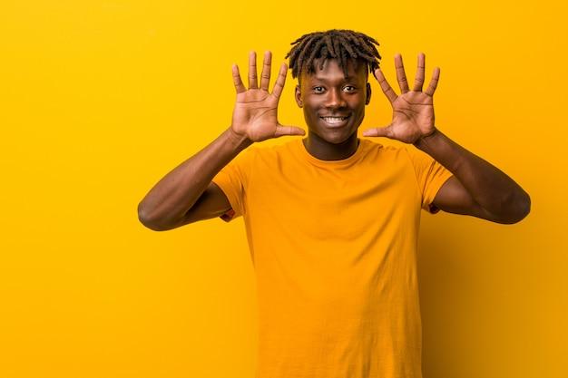 Jeune homme noir portant des rastas montrant le numéro dix avec les mains.