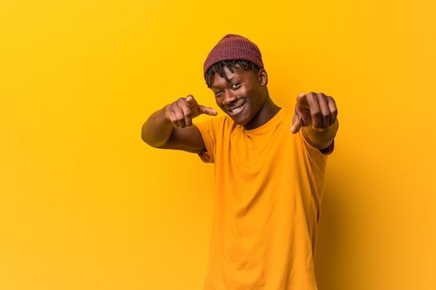 Jeune homme noir portant des rastas sur le mur jaune des sourires joyeux pointant vers l'avant.