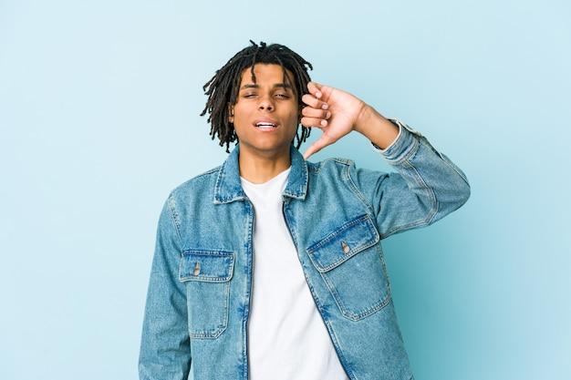Jeune homme noir portant une veste en jean montrant un geste de dégoût, les pouces vers le bas. concept de désaccord.