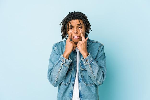 Jeune homme noir portant une veste en jean pleure, mécontent de quelque chose, de l'agonie et de la confusion.