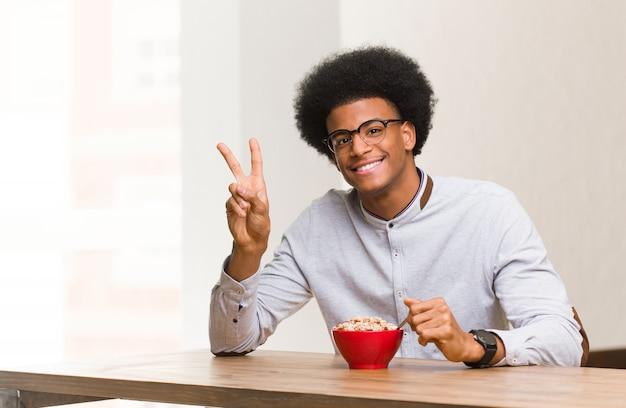 Jeune homme noir prenant son petit déjeuner faisant un geste de victoire