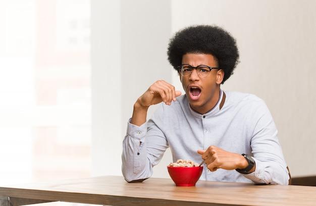 Jeune homme noir prenant son petit déjeuner en hurlant très en colère et agressif