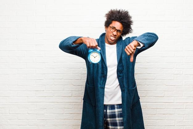 Jeune homme noir en pyjama avec réveil