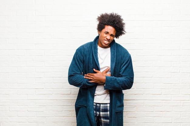 Jeune homme noir en pyjama avec une robe anxieuse, malade, malade et malheureuse, souffrant de maux d'estomac douloureux ou de grippe contre brique