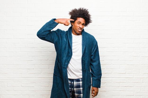 Jeune homme noir en pyjama avec une robe confuse et perplexe, montrant que vous êtes fou, fou ou que vous n'êtes pas fou contre un mur de briques