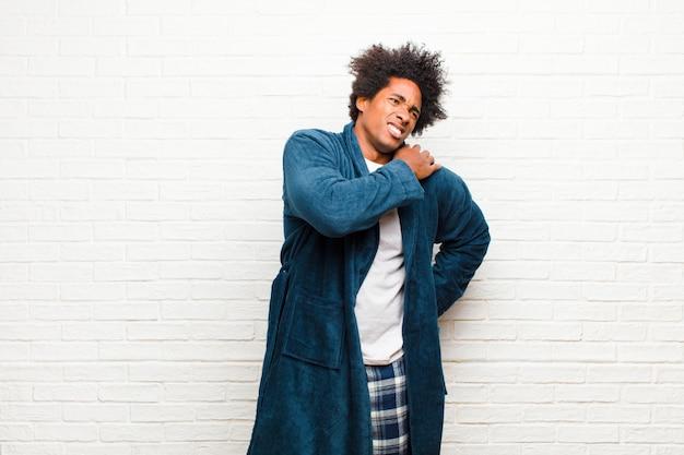 Jeune homme noir en pyjama avec une robe, fatigué, stressé, anxieux, frustré et déprimé, souffrant de douleurs au dos ou au cou contre le mur de briques