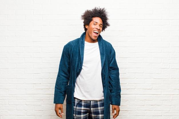 Jeune homme noir en pyjama avec une robe avec un grand sourire amical et insouciant, l'air positif, détendu et heureux, qui fait froid dans le dos