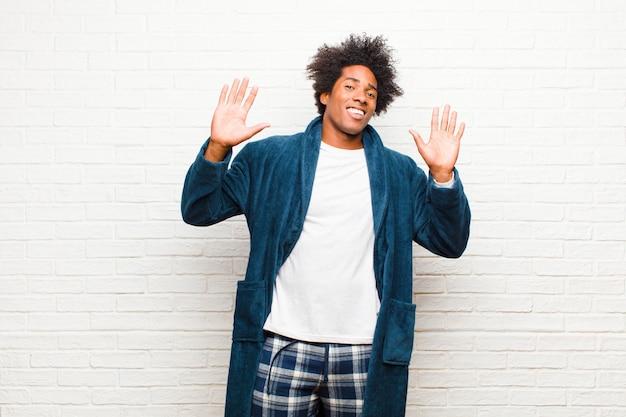 Jeune homme noir en pyjama avec une robe qui a l'air nerveuse, anxieuse et inquiète, ne disant ni ma faute ni moi-même, je ne l'ai pas fait contre un mur de briques