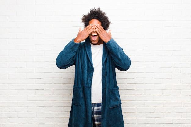 Jeune homme noir en pyjama avec une robe souriante et heureuse, couvrant les yeux avec les deux mains et attendant une surprise incroyable contre la brique