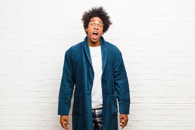 Jeune homme noir en pyjama avec une robe terrifiée et choquée, bouche grande ouverte en surprise contre un mur de briques