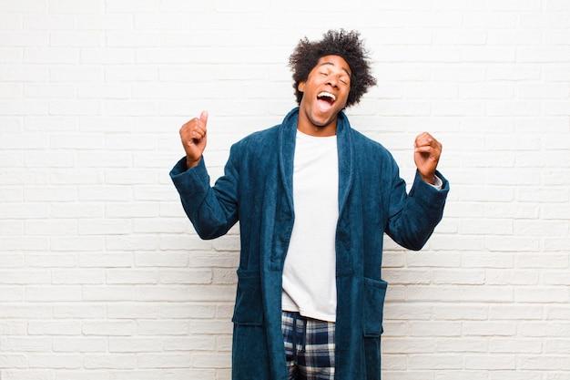 Jeune homme noir en pyjama avec une robe très heureuse et surprise, célébrant ses succès, criant et sautant contre un mur de briques