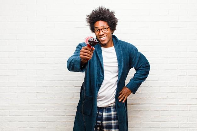 Jeune homme noir en pyjama avec un sèche-cheveux contre brique