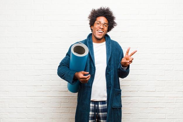 Jeune homme noir en pyjama avec un tapis de yoga