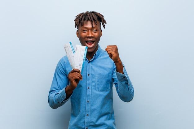 Jeune homme noir rasta tenant un billet d'avion acclamant insouciant et excité. concept de victoire.