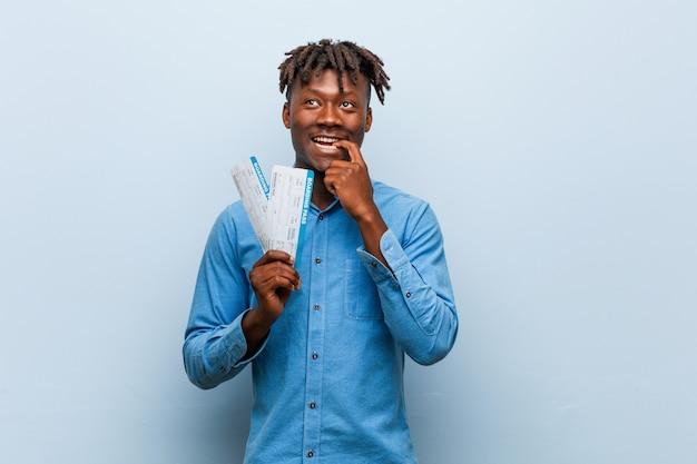 Jeune homme noir rasta tenant un billet d'avion détendu pensant à quelque chose en regardant un espace de copie.
