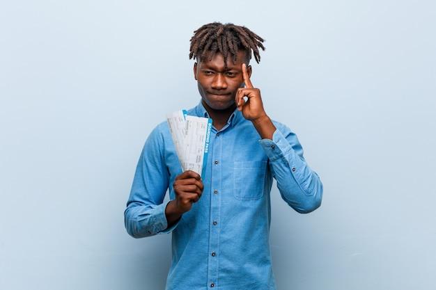 Jeune homme noir rasta tenant un billet d'avion pointant sa tempe avec le doigt, pensant, concentré sur une tâche.