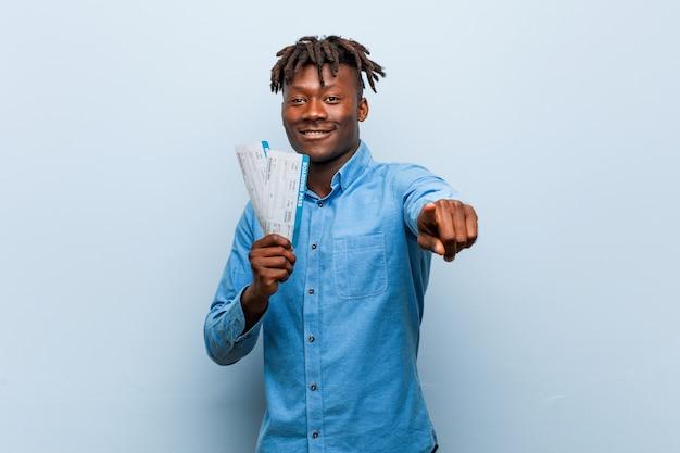 Jeune homme noir rasta tenant un billet d'avion des sourires gais pointant vers l'avant.