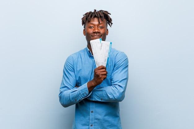 Jeune homme noir rasta tenant un billets d'avion souriant confiant avec les bras croisés.