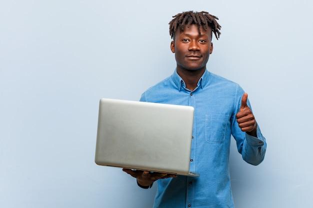 Jeune homme noir rasta tenant un ordinateur portable souriant et levant le pouce vers le haut