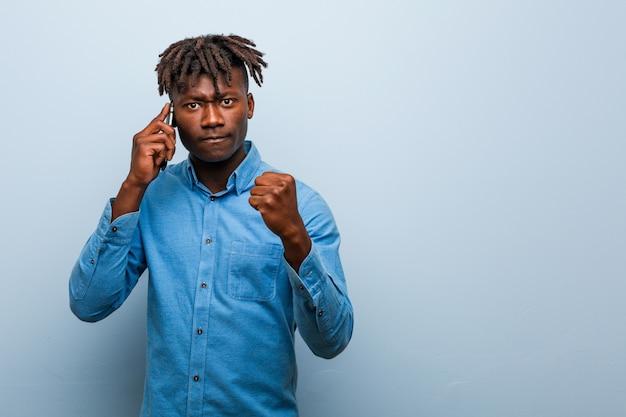 Jeune homme noir rasta tenant un téléphone montrant le poing à la caméra, expression faciale agressive.