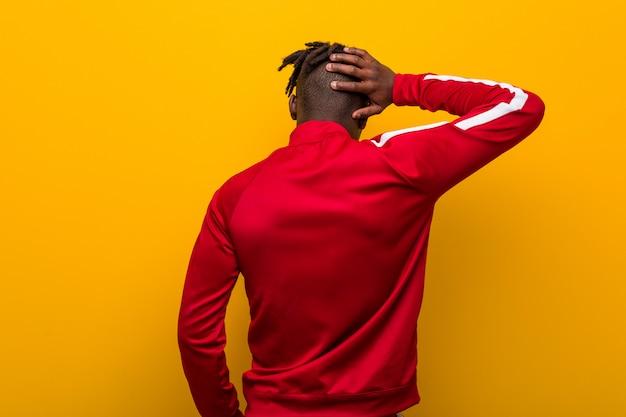 Jeune homme noir de remise en forme par derrière penser à quelque chose.