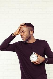 Jeune homme noir avec réveil