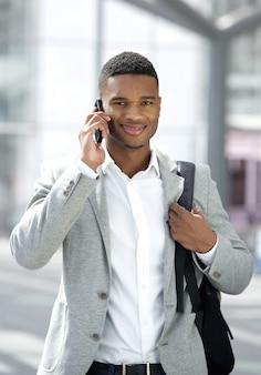 Jeune homme noir avec sac parlant sur téléphone mobile