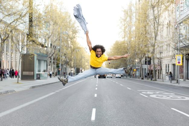 Jeune homme noir sautant énergiquement au milieu de la rue dans une grande ville. il a une coiffure afro et s'habille de façon décontractée. espace pour le texte.