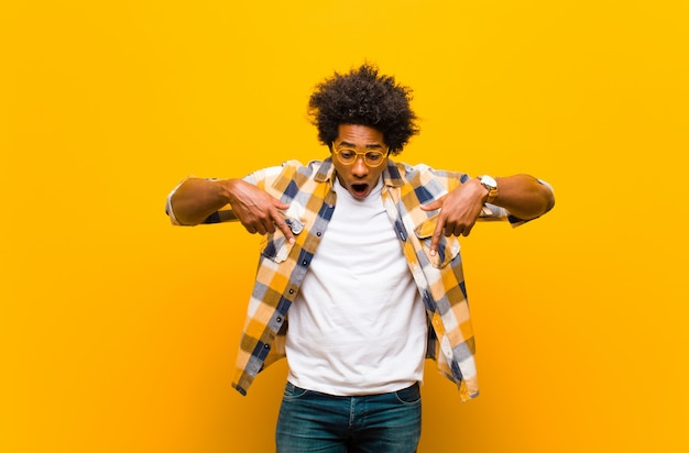 Jeune homme noir se sentant choqué, bouche bée et étonné, regardant et pointant vers le bas avec incrédulité et surprise contre le mur orange