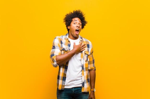Jeune homme noir se sentant choqué, étonné et surpris, la main sur la poitrine et la bouche ouverte, disant qui, moi? contre le mur orange