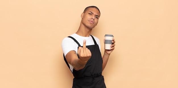 Jeune homme noir se sentant en colère, ennuyé, rebelle et agressif, retournant le majeur, ripostant