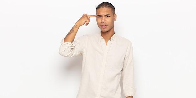 Jeune homme noir se sentant confus et perplexe, montrant que vous êtes fou, fou ou fou