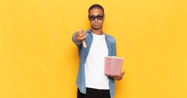 Jeune homme noir se sentant croisé, en colère, ennuyé, déçu ou mécontent, montrant les pouces vers le bas avec un regard sérieux