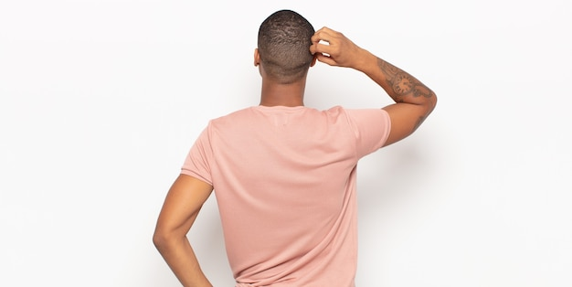 Jeune homme noir se sentant désemparé et confus, pensant à une solution, avec la main sur la hanche et d'autres sur la tête, vue arrière