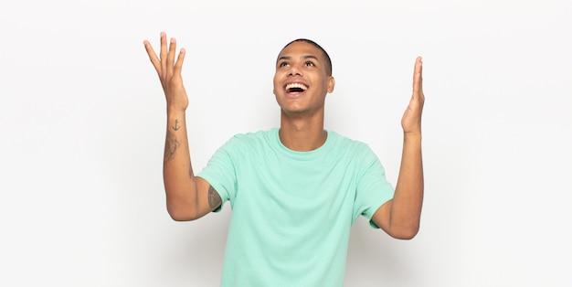 Jeune homme noir se sentant heureux, étonné, chanceux et surpris, célébrant la victoire avec les deux mains en l'air