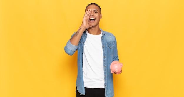 Jeune homme noir se sentant heureux, excité et positif, donnant un grand cri avec les mains à côté de la bouche, appelant
