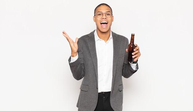 Jeune homme noir se sentant heureux, excité, surpris ou choqué, souriant et étonné de quelque chose d'incroyable