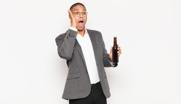 Jeune homme noir se sentant heureux, excité et surpris, regardant sur le côté avec les deux mains sur le visage