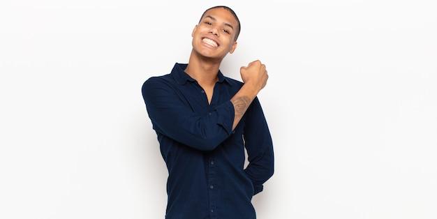 Jeune homme noir se sentant heureux, positif et prospère, motivé face à un défi ou célébrant de bons résultats