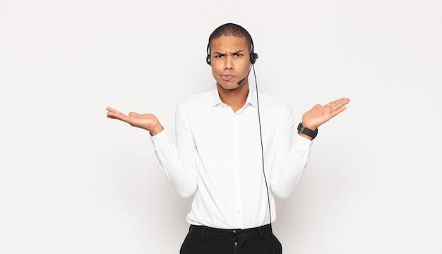 Jeune homme noir se sentant perplexe et confus, doutant, pondérant ou choisissant différentes options avec une expression drôle