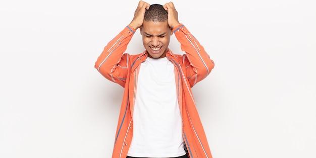 Jeune homme noir se sentant stressé et frustré, levant les mains à la tête, se sentant fatigué, malheureux et souffrant de migraine